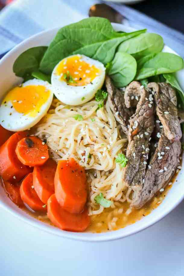 Spicy Beef Ramen Noodle Soups in bowls topped with soft boiled eggs, spinach, carrots, and beef