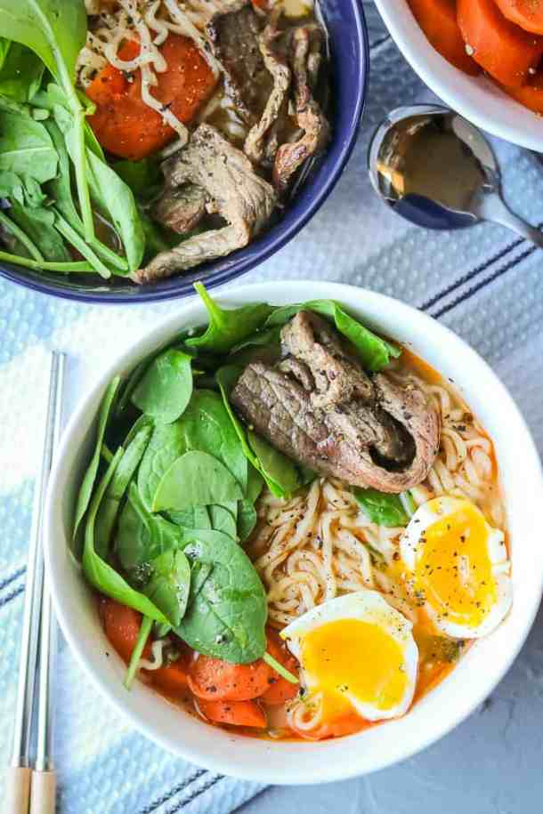 Spicy Beef Ramen Noodle Soups in bowls topped with eggs, spinach, carrots, and beef