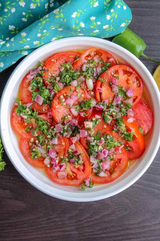Seasoned tomatoes with fresh herbs, onions and garlic on white plate ready to be served.