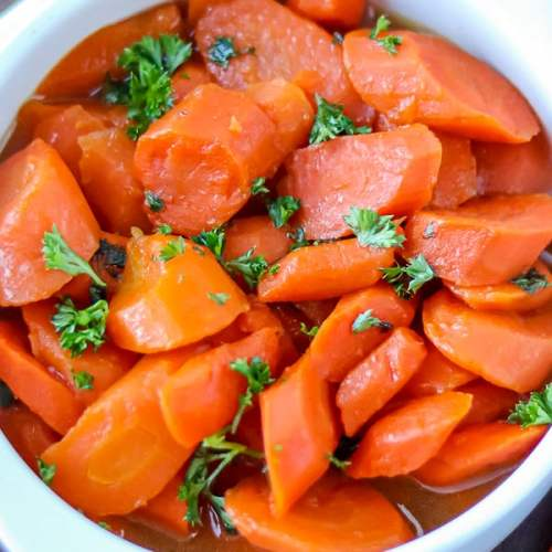 Easy glazed carrots in white bowl topped with fresh parsley