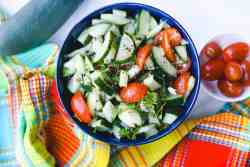 Cucumber Salad in blue bowl with cherry tomatoes on the side and colorful dishcloth