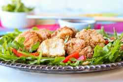 Japanese Fried chicken on a bed of mixed greens and red bell peppers