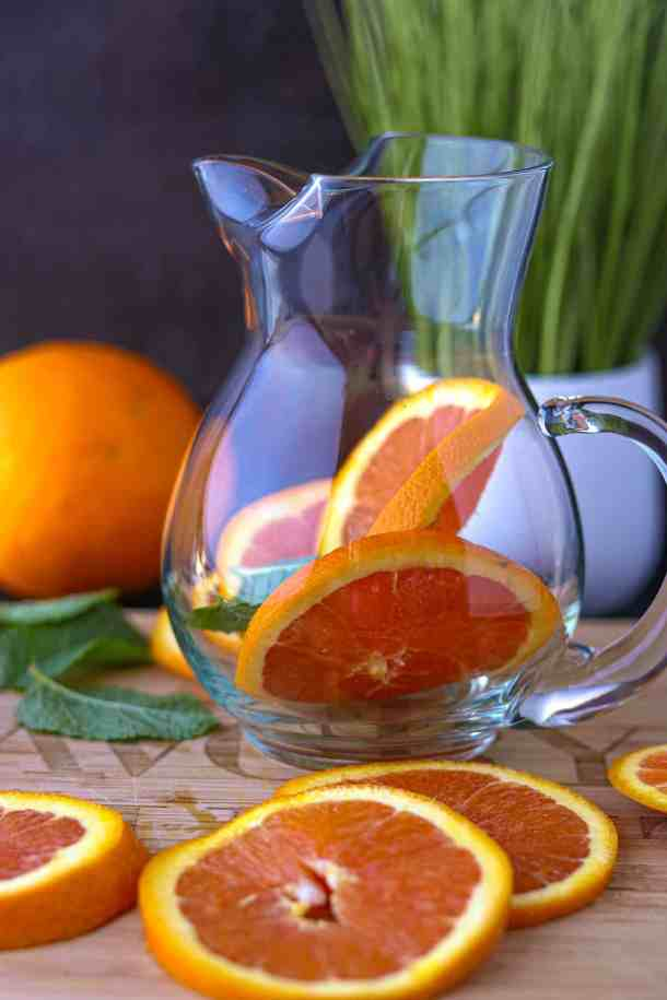 Orange and mint in pitcher with oranges slices on cutting board