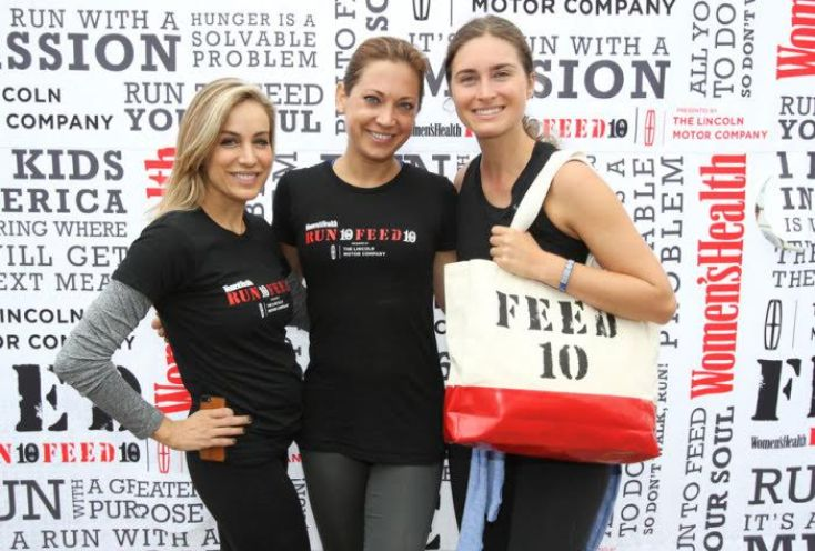 Three women posing in front of Run 10 Feed 10 poster with an event bag