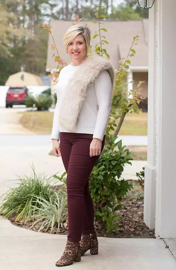 Burgundy jeans with cream sweater and faux fur scarf