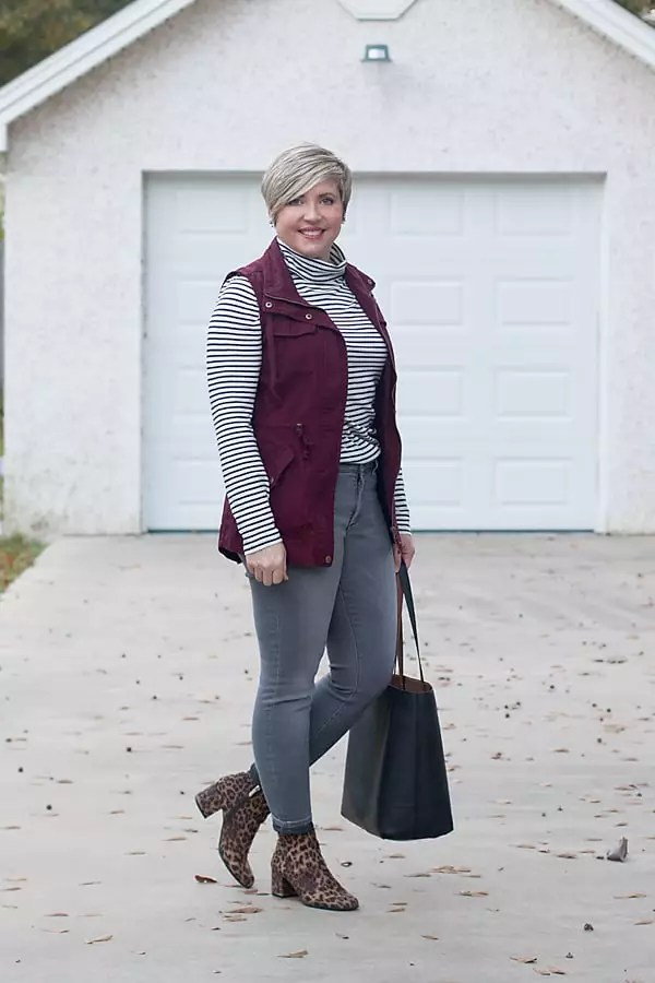 Fashion blogger in JCrew turtleneck tee, burgundy utility vest, and grey NYDJ jeans.
