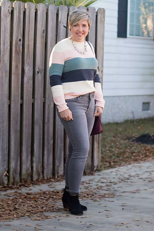 pastel color block sweater with grey jeans and statement necklace