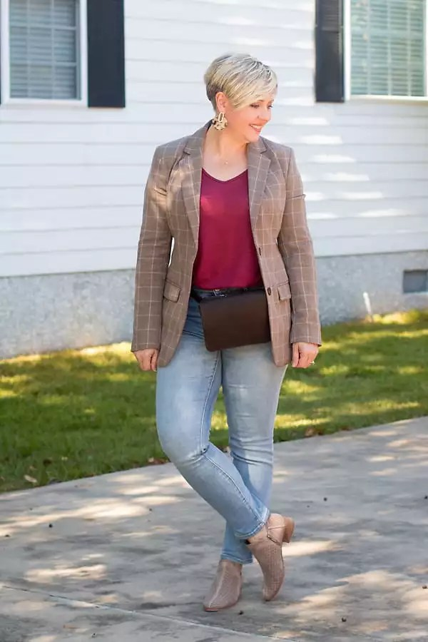 A brown plaid blazer styled with light wash jeans.