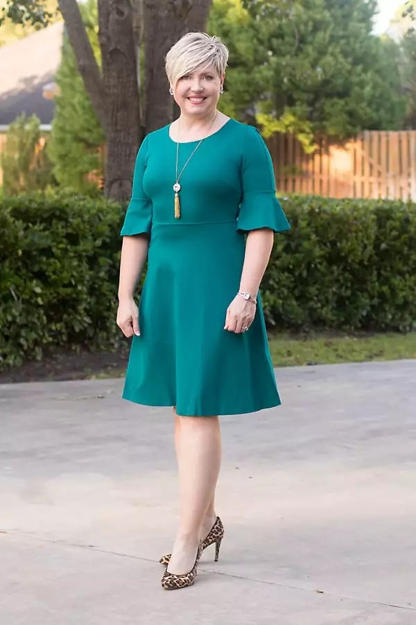 A fit and flare dress with ruffle sleeve in emerald green paired with leopard pumps that makes a great holiday outfit for the woman over 40.