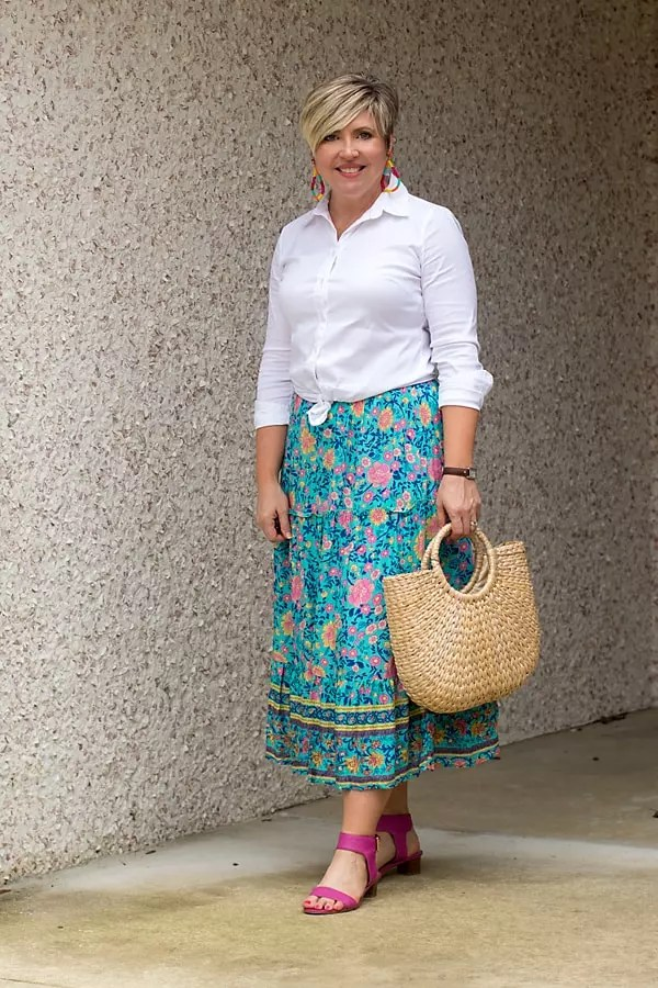 Knot a white button up shirt at the waist with a midi skirt.