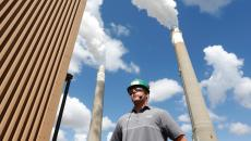 Ethan Vaagene stands between the powerplant's stacks at Great River Energy's Coal Creek Station on Wednesday, August 19, 2015, in Underwood, N.D. (Logan Werlinger/Grand Forks Herald)