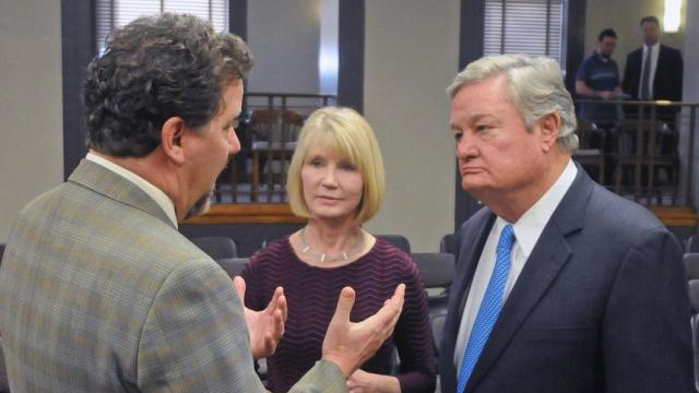 TOM STROMME/Tribune Eric Hardmeyer, left, president of the Bank of North Dakota speaks with Pam Sharp, director of the Office of Management and Budget, center, and Governor Jack Dalrymple after the governor announced a 4.05 percent cutback in spending for all state agencies to a meeting of directors of state agencies and elected officials on Monday in the Brynhild Haugland Room of the state capitol in Bismarck.