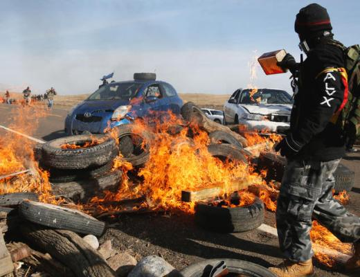 A protestor pours gasoline on a fire blocking North Dakota Hwy. 1806 on Thursday, Oct. 27, 2016, north of Cannon Ball.  Michael Vosburg / Forum Photo Editor
