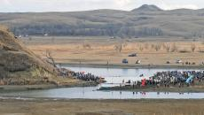 TOM STROMME/Tribune Law enforcement stand atop Turtle Hill on the Cannonball Ranch watching as protesters stand at the base while others stand across the water on Thursday afternoon in southern Morton County. A makeshift bridge placed by the protesters allowed them access to the private property.