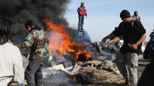 Protestors work to extinguish a fire blocking North Dakota Hwy. 1806 on Thursday, Oct. 27, 2016, north of Cannon Ball.  Michael Vosburg / Forum Photo Editor