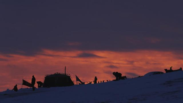 """Children sled down a hill as the sun sets inside of the Oceti Sakowin camp as """"water protectors"""" continue to demonstrate against plans to pass the Dakota Access pipeline near the Standing Rock Indian Reservation, near Cannon Ball, North Dakota, U.S., December 2, 2016.  REUTERS/Lucas Jackson"""