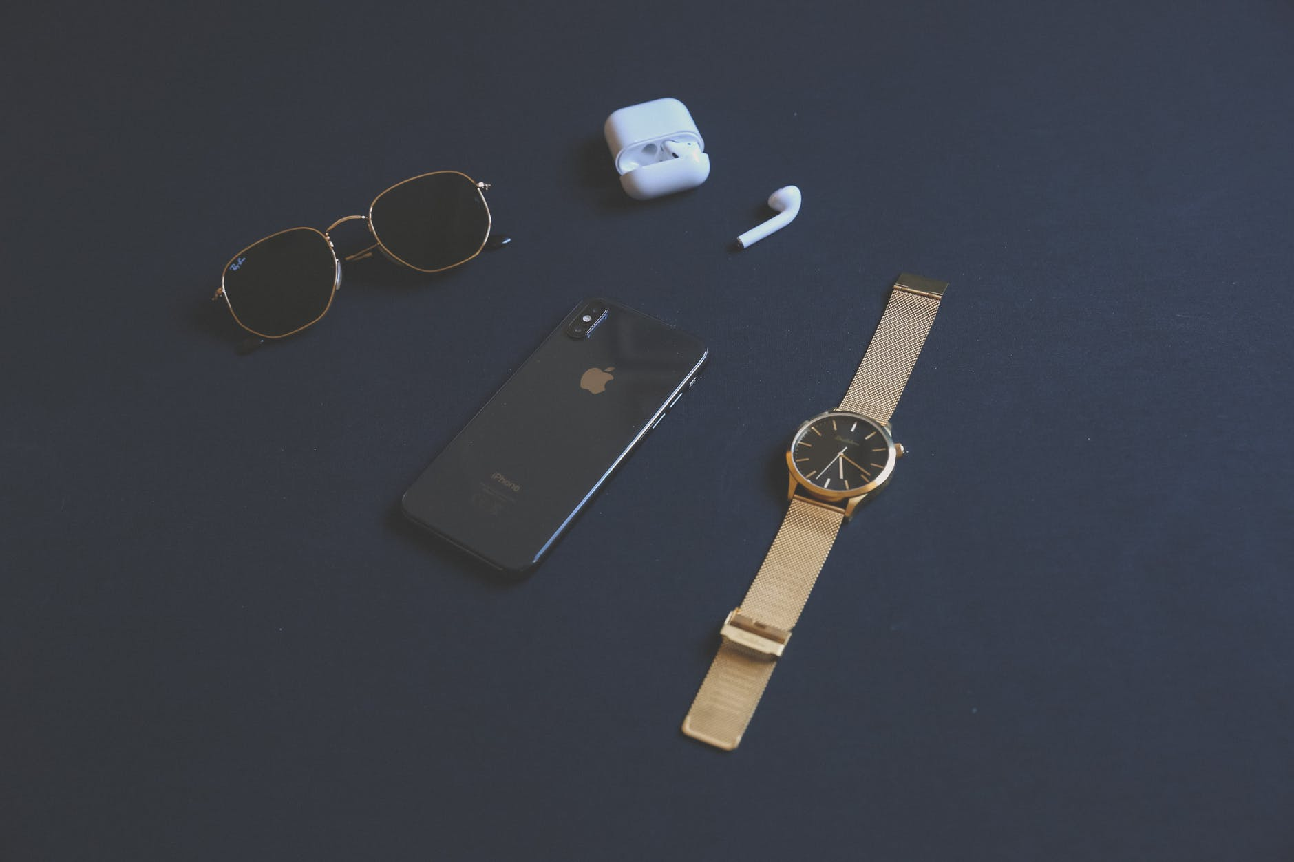 photo of iphone near sunglasses and watch