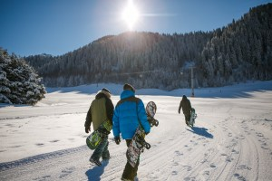 three people with snowboards; getting outside can combat depression from hearing loss