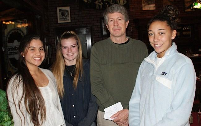 Santa Barbara High girls basketball coach Andrew Butcher is joined by team members, from left, Valerie James, Kristen Sullivan and Cassandra