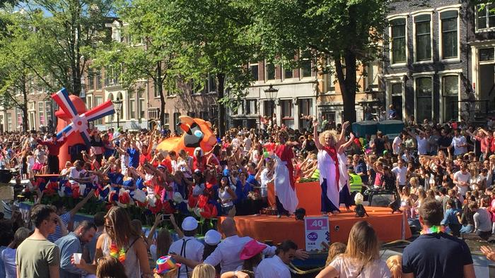 An Amsterdam pride boat motors down the canal, a drag queen is at the head of the boat and an inflatable dutch windmill in orange is at the back.