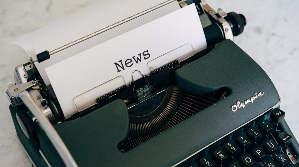 The word 'News' typed as a title on a piece of paper in a typewriter