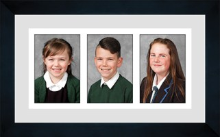 Three school portrait photographs presented in a black photo frame with a grey mount