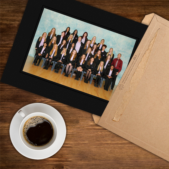 Traditional class group photograph in a black card mount being removed from a card envelope laying on a wooden table with a cup of black coffee