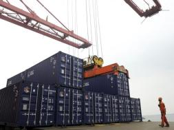A worker stands near a crane unloading shipping containers from a cargo ship at a port in Lianyungang