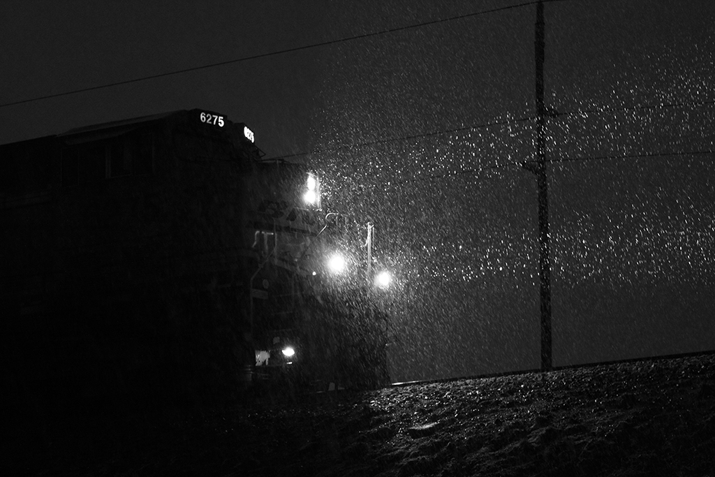 locomotive at night illuminating falling snow