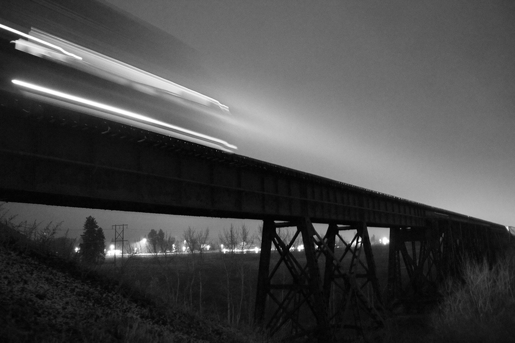 locomotive crossing bridge at night