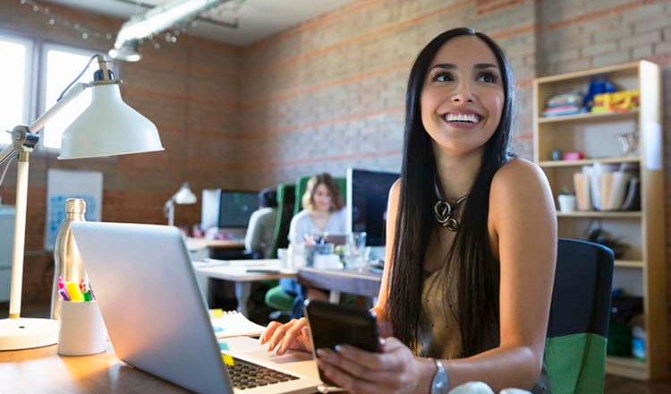Smiling creative businesswoman working at laptop in office