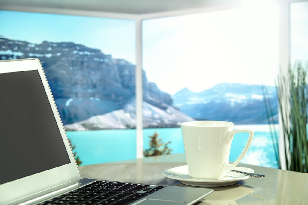 laptop and white coffee cup on table with view of blue water