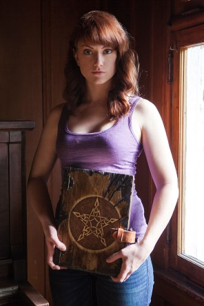 Promotional Image of Madeleine Heil with Necronomicon in Reel Nightmare