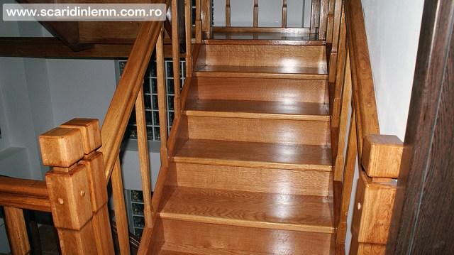 scari interioare de lemn cu mana curenta si balustrii din lemn pe vanguri inchise pe casa scarii