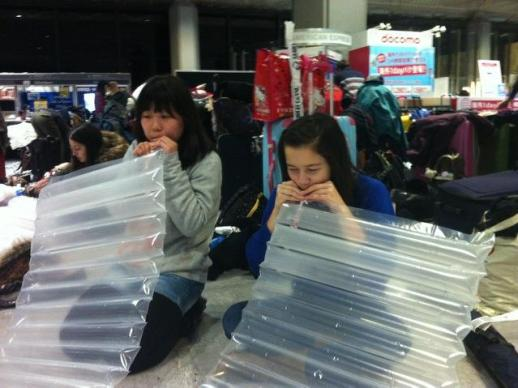 Zoe Dym (right) inflates an air mattress at the airport in Japan. Dym's flight was heavily delayed due to the storm. (Photo courtesy of Dym)