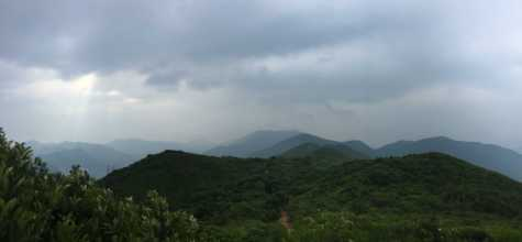 "On his hike, Manson Tung saw Hong Kong Island shrouded in clouds with Jesus Light in the upper left corner. Beyond the mountains, he said, is Central, ""the beating heart of Hong Kong."""