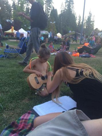This young girl stopped to listen to Leavy play the ukelele. Later, the girl wanted to try the ukelele out herself, so Leavy taught her the only chords her small fingers could actually reach.
