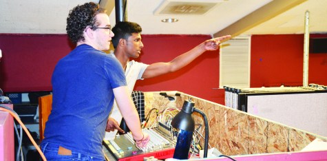 """Senior Akilan Murgesan (right) directs junior Austin Talamantes where to adjust the stage lighting in a rehearsal, while stand- ing in drama's cramped makeshift sound box. The play, """"Picasso at the Lapin Agile,"""" was March 17-18 ."""