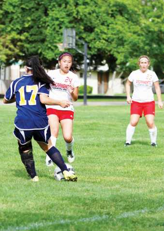 Freshman starter Micaela Chen (24) charges a player. In the third quarter, junior Avi Bhullar (left) pushes the ball down field.