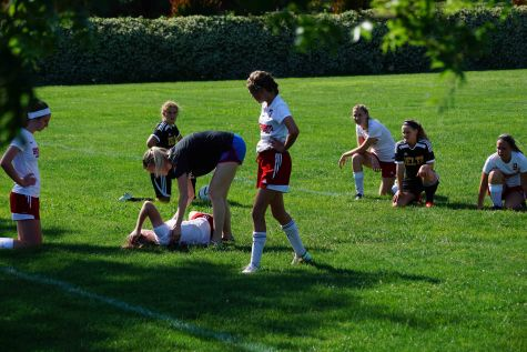 Teammates look on as assistant coach Gabriella Foster helps sophomore Evann Rudek, who hyperextended her knee.