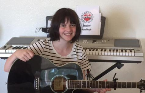 Freshman Mackenzie McLeod sits in front of her piano while holding her guitar. McLeod knows how to play both instruments.