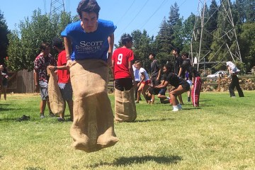 Junior Nate Leavy jumps in mid-air in the sack race. (Photo by Sanjana Anand)