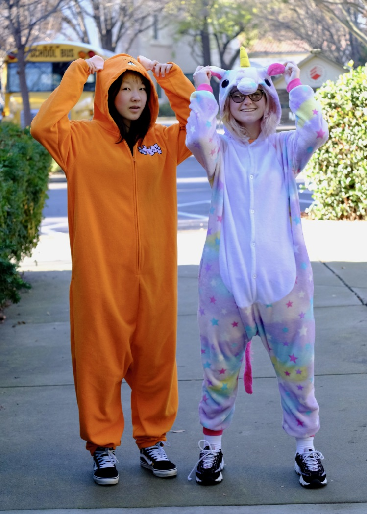 Junior Hermione Xian and freshman Stella Fluetsch stay warm in onesies on pajama day.