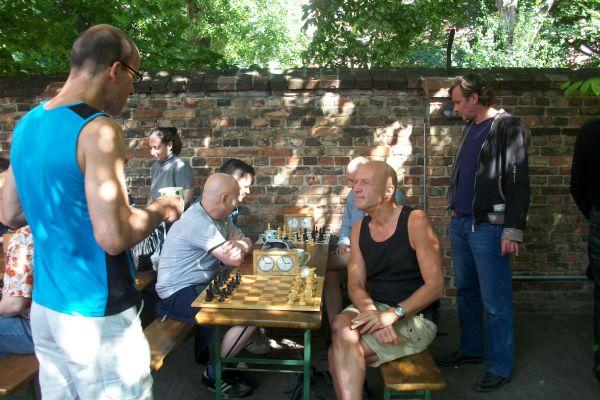 Kurz vor Rundenbeginn verfolgen die Spieler verschiedene Strategien. Einige sitzen am Brett, andere befinden sich draußen an der frischen Luft.