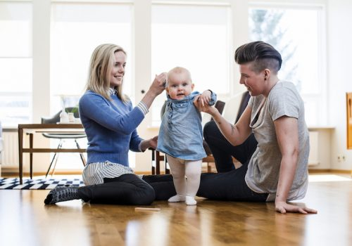 A photo of lesbian couple assisting baby to walk at home. Homosexual couple is with cute toddler. Family of three is at brightly lit room.