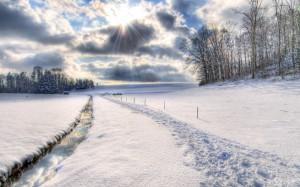 HDR-Foto eines schmalen Bachs, der sich schnurgerade neben einem Weg durch eine sonst unberührte Schneelandschaft zieht, rechts ein Waldrand, hinten ein anderer Wald mit einer Hütte. Himmel wolkig mit durchbrechenden Sonnenstrahlen