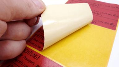 Rote Ölbeständige Etiketten mit Warnhinweisen, von denen eines abgezogen wird