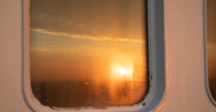 Reflektion des Sonnenaufgangs im Bullauge