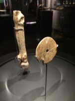 A roundel and a spear-thrower carved with a deer