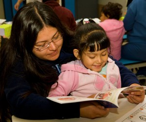A mother reads a book to her young daughter in a cafeteria.